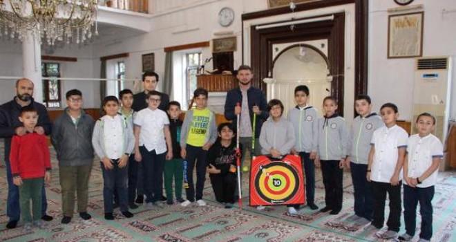 Camide çocuklara ok atma eğitimi